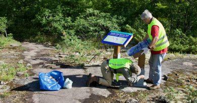 Bernard Proulx and Marc Savard install trailhead signs.