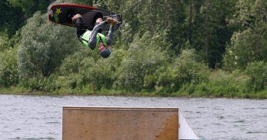 A photo of Jordan Sien doing a flip on a wakeboard.