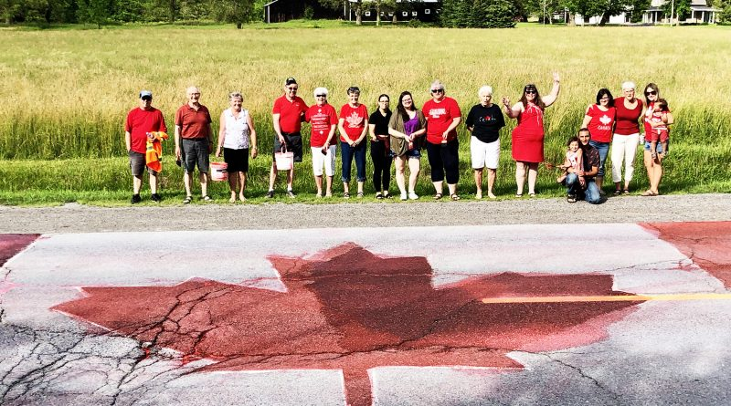 Painters pose with their road-sized Canada Day flag painting.