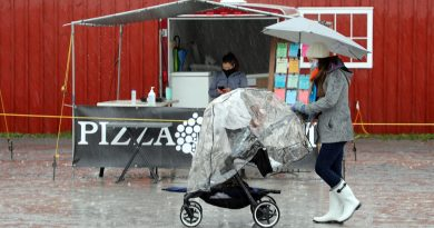 A mom and her baby walk during a rainy day.