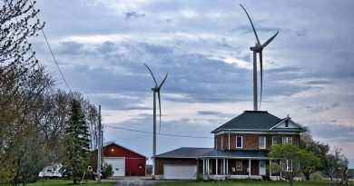 A photo of wind turbines behind a house.
