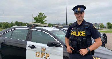 Const. Prohet poses in front of a cruiser.