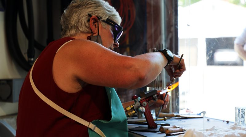 Roxanne Ward torches a glass bead.