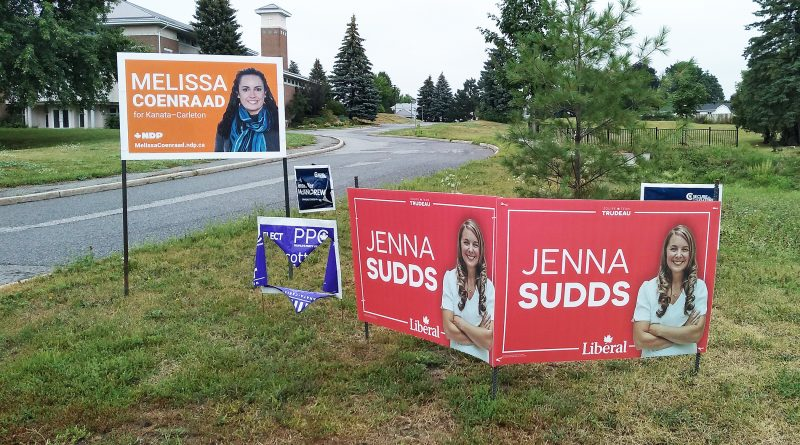 A photo of five elections signs with one damaged.
