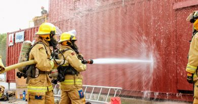 Two FFIT participants learn how to work a fire hose.