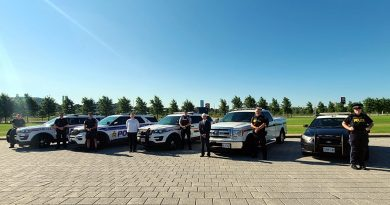 A photo of four police forces and their vehicles.