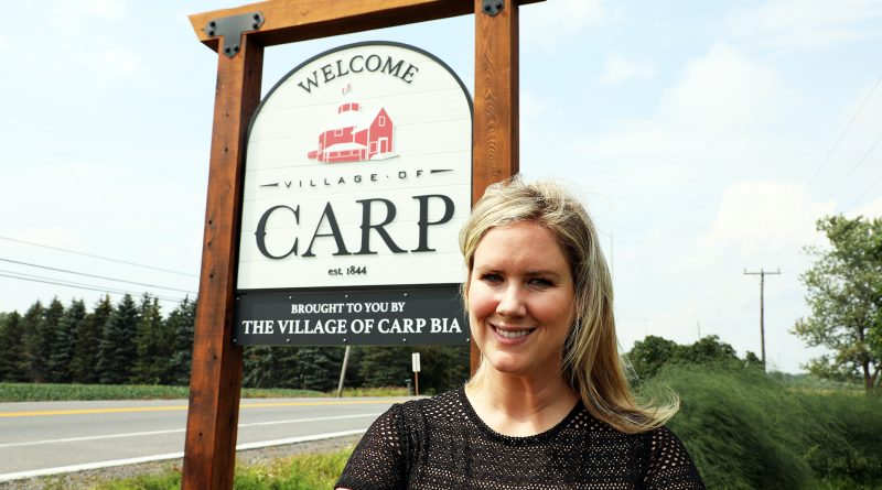 Carp's Jennifer Stewart poses in front of a newly erected village sign, installed the first week of August as part of a recent BIA project. Photo by Jake Davies