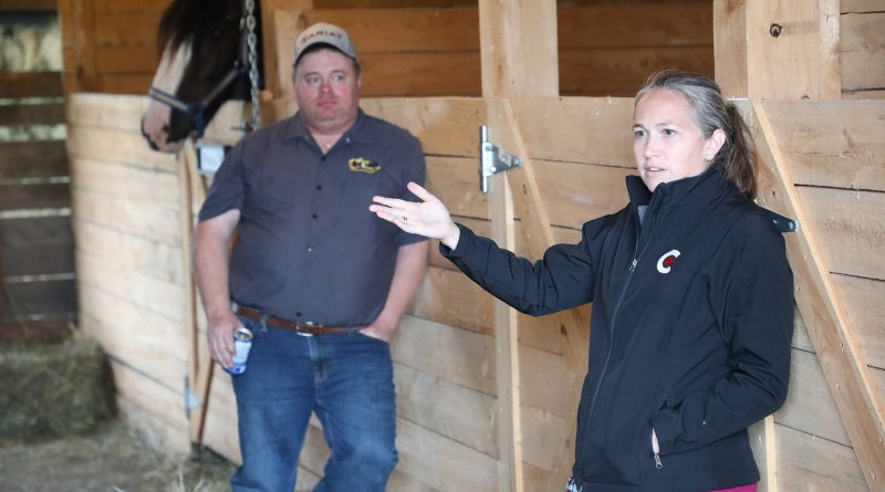 A photo of Jennifer McAndrew speaking with Joey Wilson looking on.