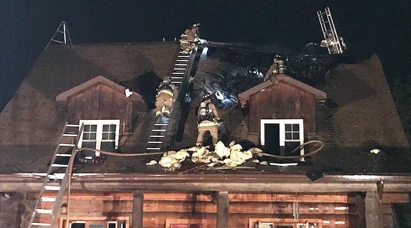 Firefighters fight a blaze on the top of a log home's roof.