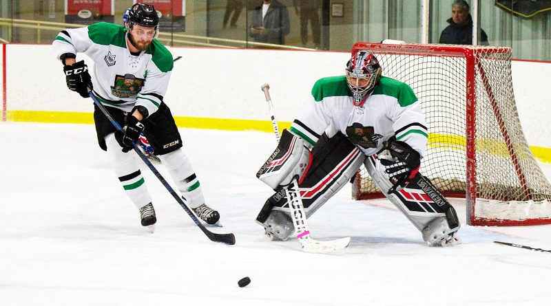 A goalie and defencemen skate with the puck.