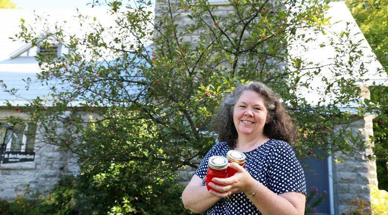 Kirstin Davidson poses in front of the church's crab apple tree.