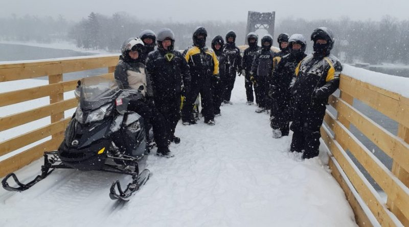 A photo of snowmobilers on the bridge.