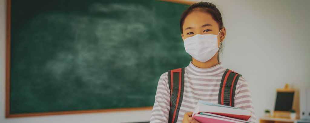 A young student in school wears a mask.